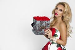 一件典雅的晚礼服的美丽的白肤金发的妇女有英国兰开斯特家族族徽的,拿着华伦泰的礼物,与花的一flowerbox beauvoir 免版税库存图片