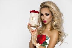 一件典雅的晚礼服的美丽的白肤金发的妇女有英国兰开斯特家族族徽的,拿着华伦泰的礼物,与花的一flowerbox beauvoir 库存照片