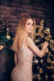一件典雅,苗条的金子晚礼服的年轻愉快的微笑的妇女装饰与微笑somtret的一棵圣诞树对cmaera  库存照片