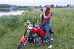 一件减速火箭的盔甲的女孩坐有照相机的葡萄酒摩托车 库存照片