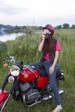 一件减速火箭的盔甲的女孩坐有照相机的葡萄酒摩托车 免版税图库摄影