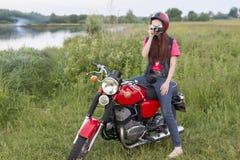 一件减速火箭的盔甲的女孩坐有照相机的葡萄酒摩托车 免版税库存图片