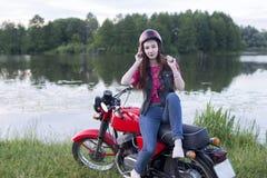 一件减速火箭的盔甲的女孩坐葡萄酒摩托车户外 免版税图库摄影