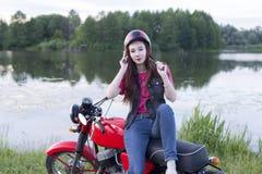 一件减速火箭的盔甲的女孩坐葡萄酒摩托车户外 免版税库存照片