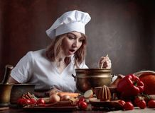 一件厨师制服的年轻美丽的女孩有老黄铜平底锅和w的 免版税库存照片