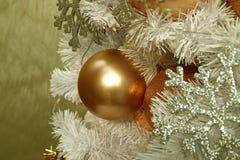 一件发光的桃红色金子球形的圣诞节装饰品的特写镜头与被弄脏的银色闪烁雪花装饰品的 免版税库存照片