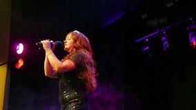 一件发光的黑礼服的一位年轻红发女演员在阶段唱歌在一阵烟幕的话筒 股票录像