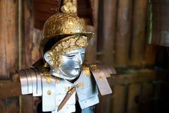 一件古老罗马四个一组的盔甲的复制品对日志木墙壁 免版税库存图片