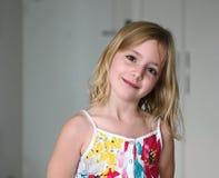 一件夏天白色礼服的六岁的白肤金发的女孩有花的微笑在抽象背景的 图库摄影
