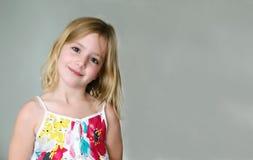 一件夏天白色礼服的六岁的白肤金发的女孩有花的微笑在抽象背景的 免版税图库摄影