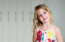 一件夏天白色礼服的六岁的白肤金发的女孩有花的微笑在抽象背景的 免版税库存图片