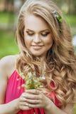 一件夏天礼服的美丽的少女在日落 在森林模型的时尚照片在一件桃红色长的礼服,有流动的卷发的 免版税库存图片
