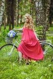 一件夏天礼服的美丽的少女在日落 在森林模型的时尚照片在有花花束的一辆自行车,在一桃红色l 图库摄影