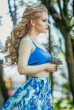 一件夏天礼服的美丽的少女在日落 在森林模型的时尚照片在蓝色顶面和长的裙子,有流动的头发的 免版税图库摄影