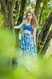 一件夏天礼服的美丽的少女在日落 在森林模型的时尚照片在一条蓝色上面和长的裙子,有流动的古芝的 免版税库存照片