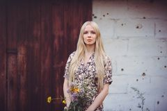 一件夏天礼服的美丽的少妇有在墙壁背景的野花的与从看照相机的子弹的孔 Aggre 免版税库存照片