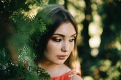一件夏天红色礼服的美丽的女孩在公园 免版税库存图片