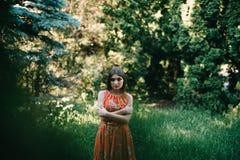 一件夏天红色礼服的美丽的女孩在公园 免版税图库摄影