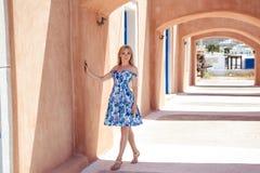 一件夏天蓝色礼服的美丽的白肤金发的妇女在南欧洲 库存图片