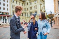 一件外套的一个年轻人在街道上谈话与女孩 免版税库存照片