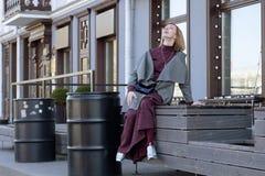 一件外套的愉快的妇女在城市 免版税库存图片