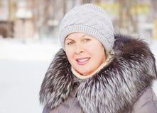 一件外套的美丽的妇女有毛皮衣领和一个被编织的帽子的 免版税库存照片