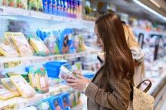 一件夹克的年轻女商人在拿着土耳其的包裹的商店,读构成 库存图片