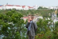 一件夹克的想法的小男孩反对海、树和一个老城市的背景 免版税库存照片