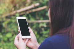 一件妇女藏品和使用有空白的黑屏幕的白色巧妙的电话的大模型图象在室外和绿色自然 库存照片