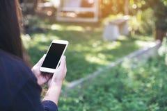 一件妇女藏品和使用有空白的黑桌面屏幕的白色巧妙的电话的大模型图象在室外与绿色自然 免版税库存图片