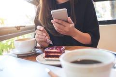 一件妇女藏品,使用和看巧妙的电话的特写镜头图象,当吃与加奶咖啡杯子和膝上型计算机时的一个蛋糕 免版税库存图片