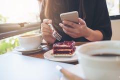 一件妇女藏品,使用和看巧妙的电话的特写镜头图象,当吃与加奶咖啡杯子和膝上型计算机时的一个蛋糕 库存照片