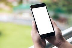 一件妇女` s手藏品和使用有空白的白色屏幕的黑巧妙的电话的大模型图象,当站立在阳台时 图库摄影