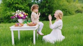 一件巧妙的礼服的一个小女孩在手上快乐地坐桌和戏剧与她的母亲 圣帕特里克` s日 影视素材