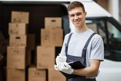 一件年轻英俊的微笑的工作者佩带的制服在搬运车拿着在他的箱子旁边充分站立一张剪贴板 免版税图库摄影