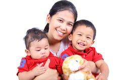 一件愉快的母亲藏品她的二个小男孩。 免版税图库摄影