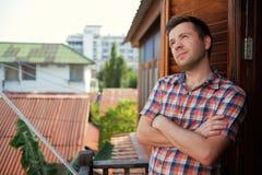 一件方格的衬衣的年轻人在阳台站立在与在胸口神色交叉的双臂的一个晴天梦想  免版税库存照片