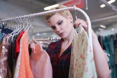 一件时兴的礼服的美丽的健美丰满的女孩走在商店的和选择新的衣裳,看在挂衣架的时髦服装  库存图片