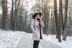 一件时髦的帽子和外套的年轻美丽的女孩走在wi的 免版税库存图片