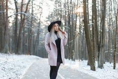 一件时髦的帽子和外套的年轻美丽的女孩走在wi的 库存照片