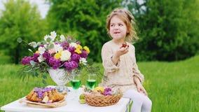 一件明亮的巧妙的礼服的逗人喜爱的小女孩坐桌并且吃有巧克力甜点的手 圣帕特里克` s天野餐 股票视频