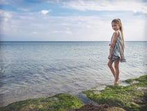 一件明亮的礼服的十几岁的女孩由海 您系列节日快乐的夏天 免版税图库摄影