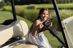 一件明亮的礼服的小女孩微笑,当坐对高尔夫球汽车的轮子的时 库存照片