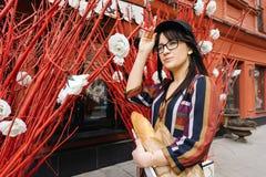 一件明亮的礼服的年轻长发深色的妇女对红色墙壁 免版税库存照片