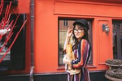 一件明亮的礼服的年轻长发深色的妇女 免版税库存照片