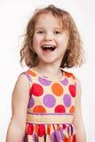 一件明亮的礼服的愉快的小女孩 免版税库存图片
