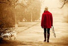 一件明亮的红色外套的女孩走在有一条狗的公园的在分类 免版税库存图片