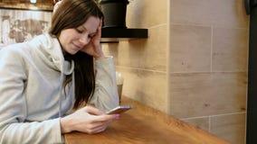 一件明亮的衬衣的微笑的年轻深色的妇女按摩在她的手机的坐在咖啡馆 股票视频