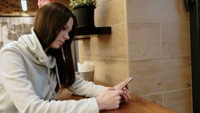 一件明亮的衬衣的沉思年轻深色的妇女读在她的坐在咖啡馆的手机的消息 影视素材