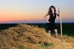 一件晚礼服的女孩与干草叉 免版税库存图片